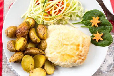 Hermelín obaľovaný v lístkovom ceste ochutený bylinkami a rastlinnými olejmi podávaný s pečenými lahôdkovými zemiakmi ochutenými maslom, brusnicami a zeleninou